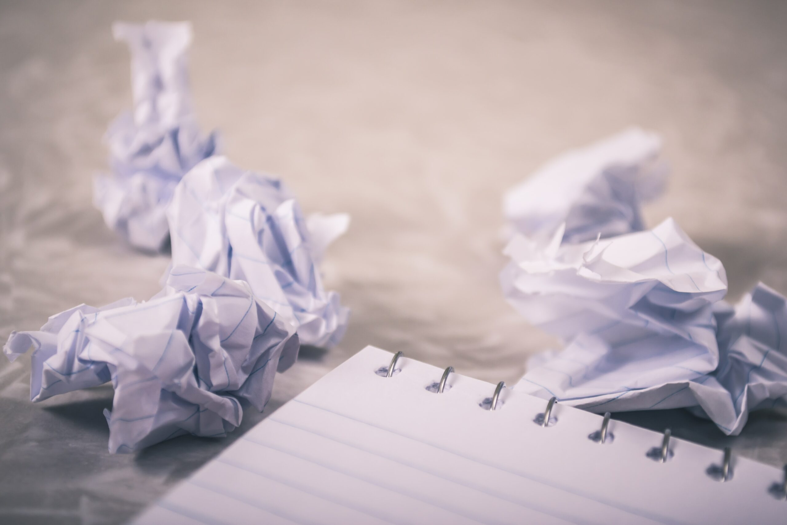 crumpled white paper on brown wooden table