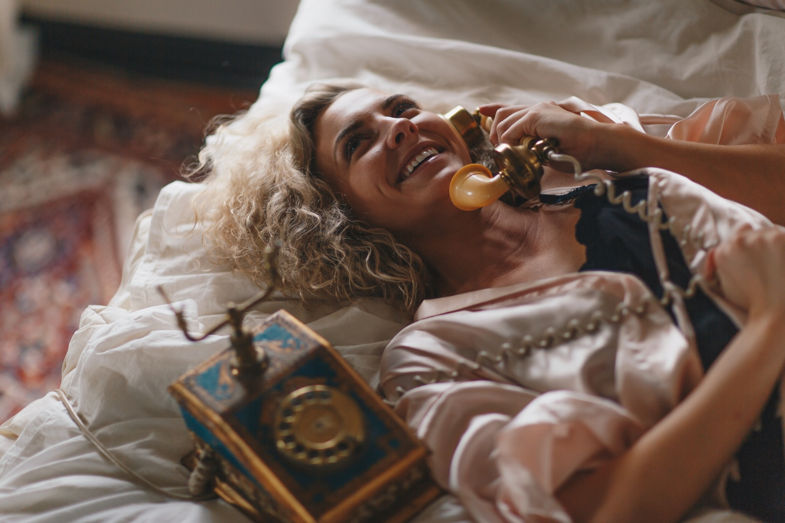 woman laying on white bed using a brown telephone